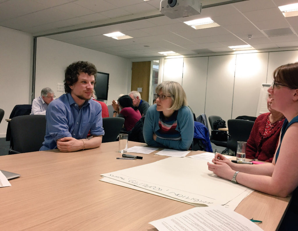 Attendees in discussion at the listening event